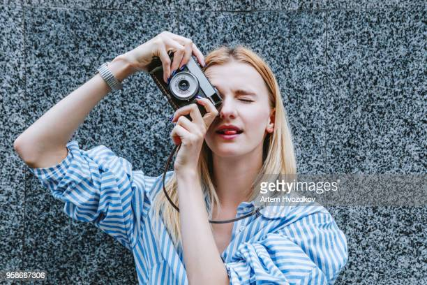 the girl carefully shoots on a film camera - photographic film camera stock photos and pictures