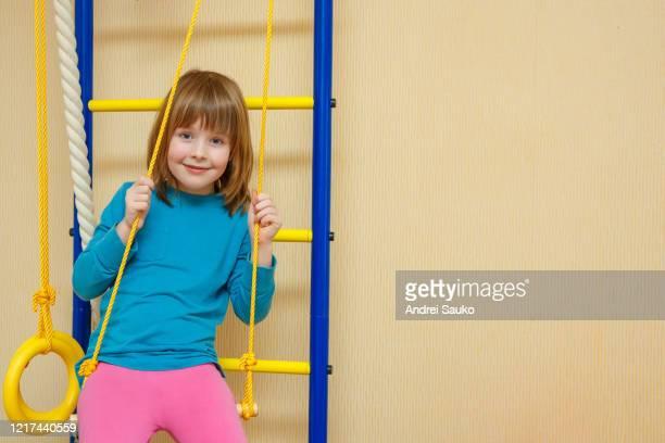 girl cheerfully sits sports ladder girl