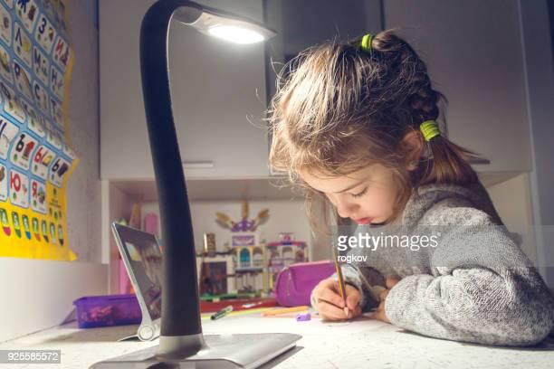 La niña dibuja en la mesa a la luz de la lámpara