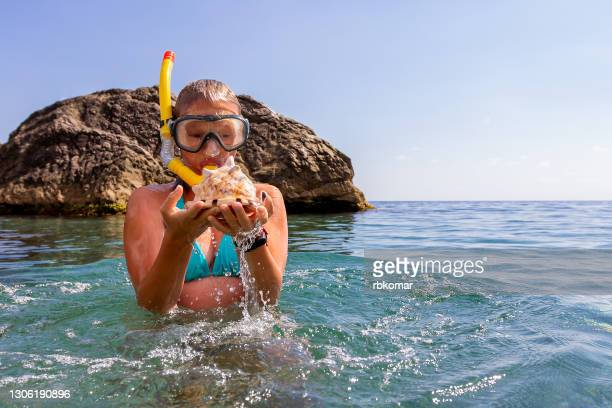 the girl found a huge beautiful shell in the sea. swimming with a snorkel and a mask - underwater stock pictures, royalty-free photos & images