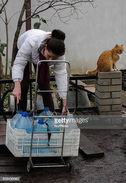 The girl fulfills the plastic bottles with water from town's only working water source in the Avdiivka suburb Civilians who came to the town's only...