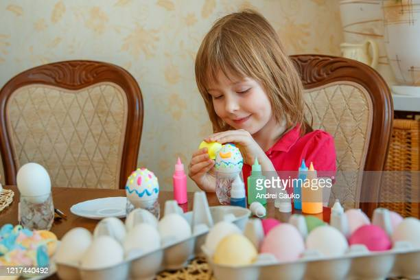 girl is fun painting eggs for