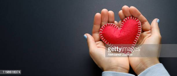 the girl is holding a red handmade heart on a black background. banner. - representing stock pictures, royalty-free photos & images