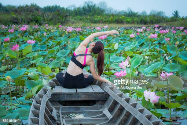 The girl is practicing yoga with different movements on the lotus pond under the sunrise.