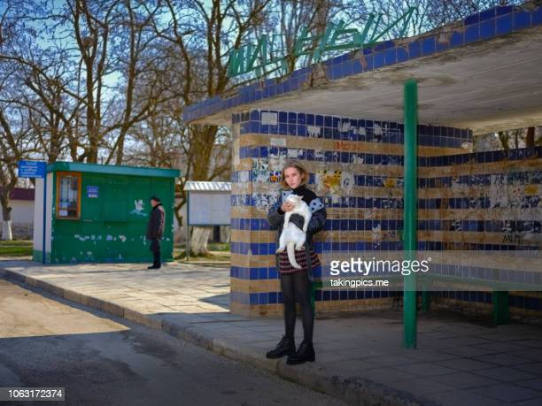 The girl is standing at the bus stop