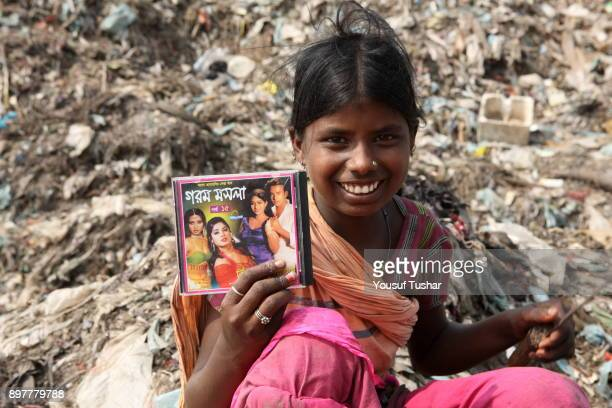 The girl is very happy because she finds her favourite artists CD album from dump yard She collects rubbish for sale At the end of the day she earns...