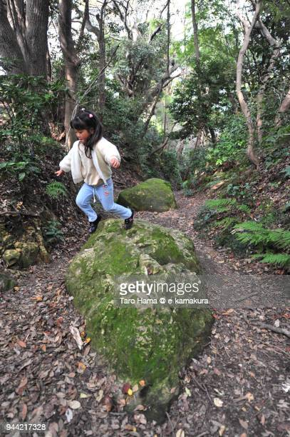 The girl jumping from the stone on the ancient road in Kamakura in Japan