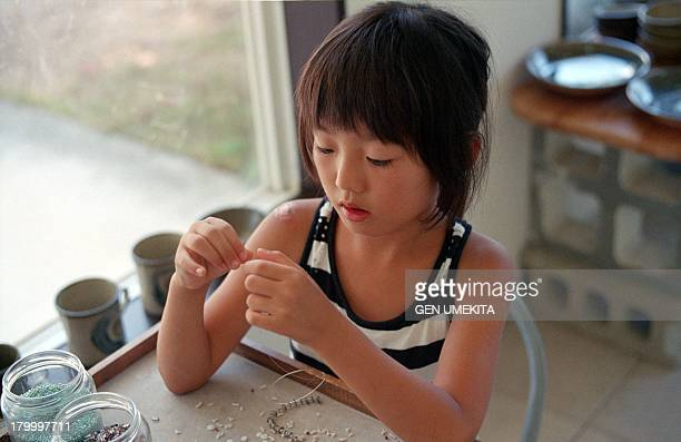 the girl making bead accessories - ビーズ ストックフォトと画像