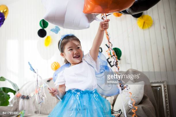 The girl seems to have fun wearing a butterfly costume and holding a balloon in one hand.