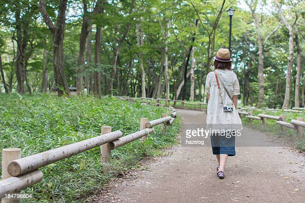 The girl walking among park trees
