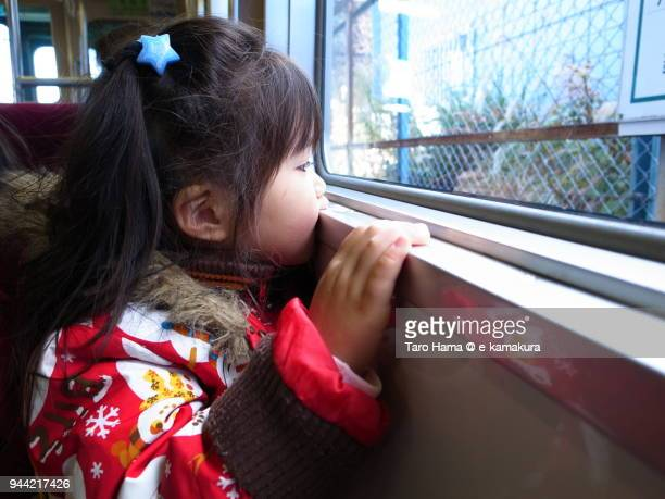The girl watching out the scenery from the train in Japan
