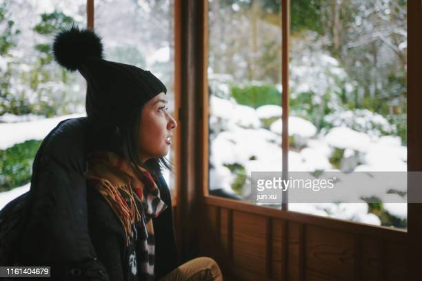 the girl watching the snow in the cabin - スキー板 ストックフォトと画像