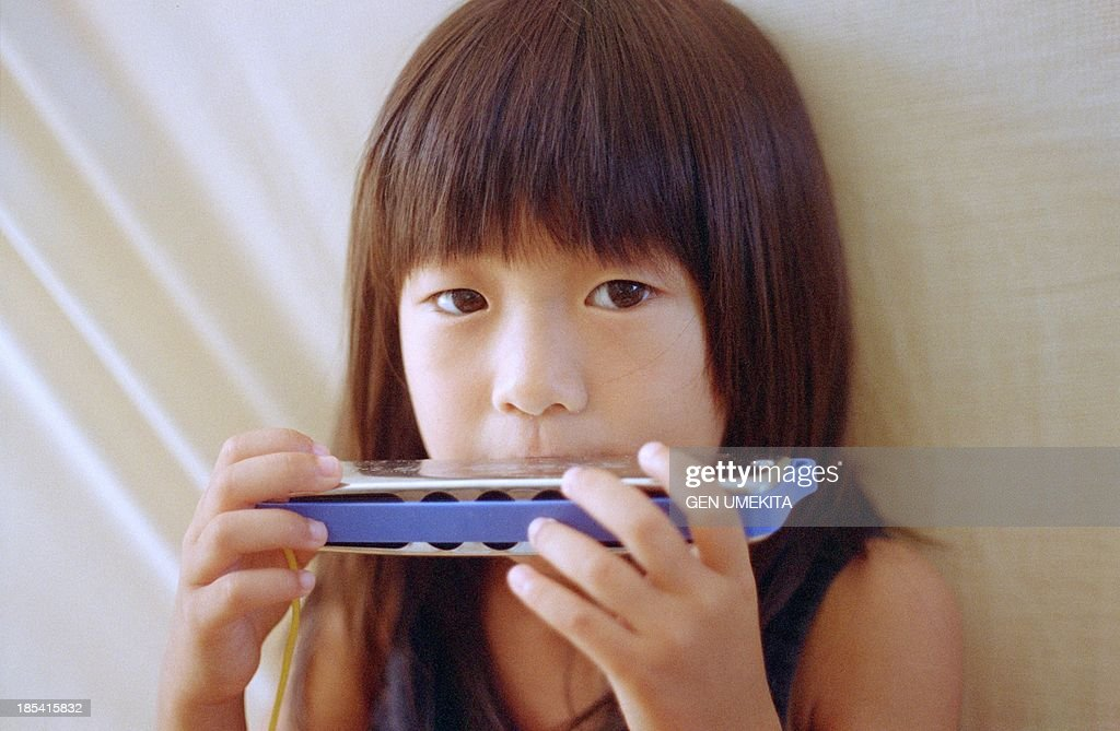 The girl who play a harmonica : Stock Photo