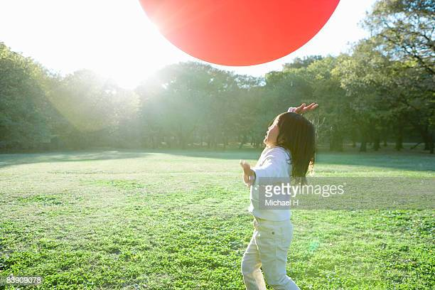 The girl who plays a  big balloon in a park of