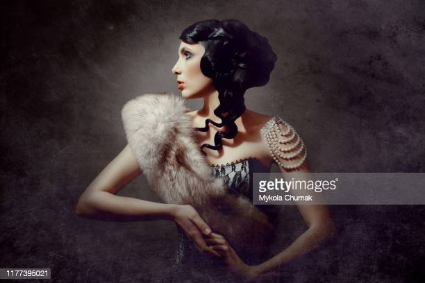 the girl with creative retro hairstyle  fur corset  and epaulettes of beads on gray studio background with skratches - 肩章 ストックフォトと画像