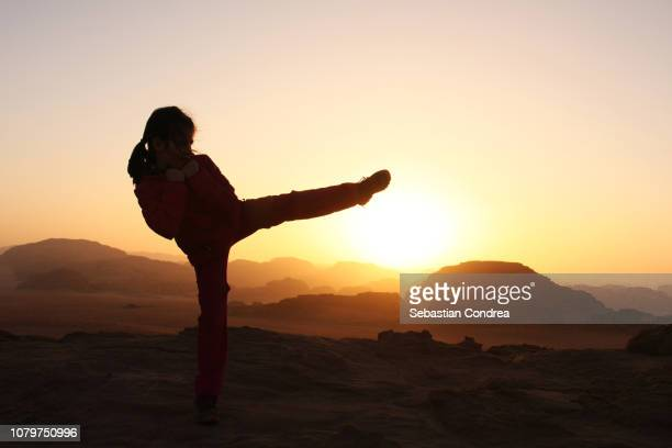 the girl with her leg in the ahp cha-gi position, practicing taekwondo at sunset in wadi rum desert, jordan - artes marciais imagens e fotografias de stock