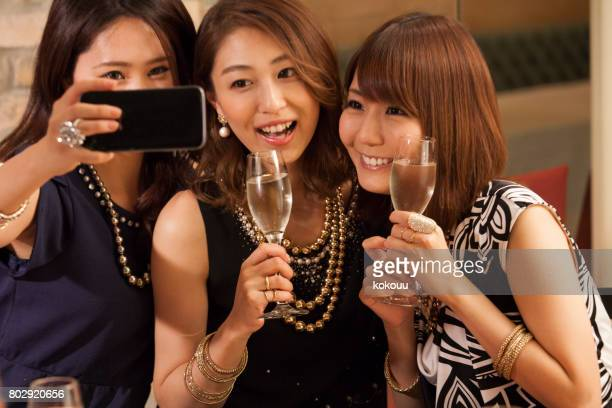 The girls take pictures with smartphones.