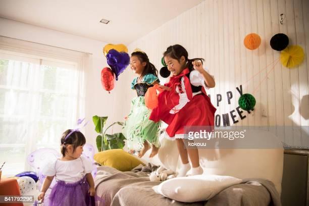 プリンセスの衣装を身に着けている女の子がソファーでダンスします。