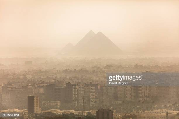The Giza Pyramids poke above the buildings of Giza on September 24 2017 in Cairo Egypt Overview photos of Cairo's buildings cityscape and...