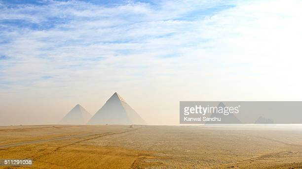 The Giza pyramids viewed from distance in morning haze and blue skies