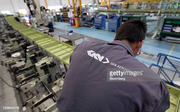 The GKN Aerospace logo is seen on the overalls of an employee as he works on a trailing wing edge of an Airbus SAS A380 aircraft a unit of European...
