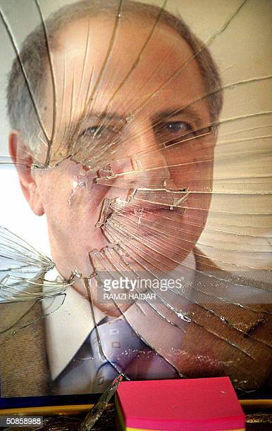 The glass in a portrait of Iraqi Governing Council member Ahmed Chalabi is seen smashed after Iraqi police and US troops raided his head office in...
