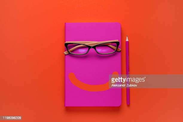 the glasses are lying on a pink notebook, next to a pencil, against a background of lush lava. a painted smile on a notepad. workplace freelancer, businessman, entrepreneur. - literatur stock-fotos und bilder