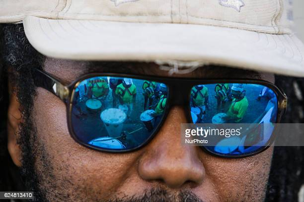 The glasses of a member of the musical group Lamento Negro reflects the Maracatu drums Afrodescendent musical groups make a presentation in honor of...