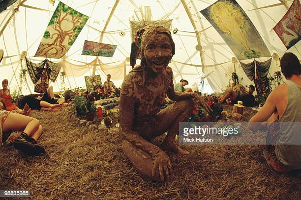 The Glastonbury Festival in June 1993 showing a naked woman covered in mud with friends inside a tent