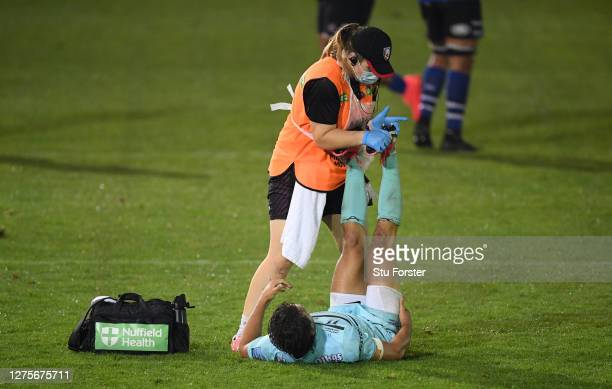 The Gloucester physio wearing PPE gives treatment to Gloucester player Lloyd Evans during the Gallagher Premiership Rugby match between Bath Rugby...