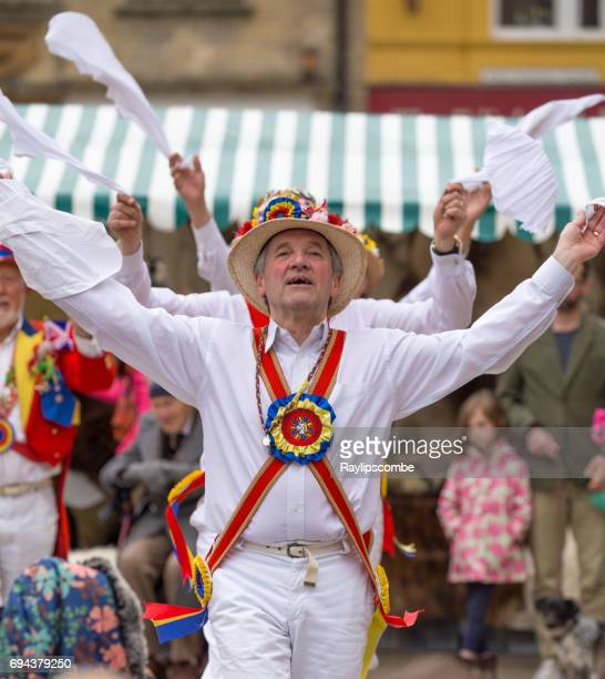 the gloucestershire morris men performing a traditional dance at the fleece fair in cirencester market place - mayday stock photos and pictures