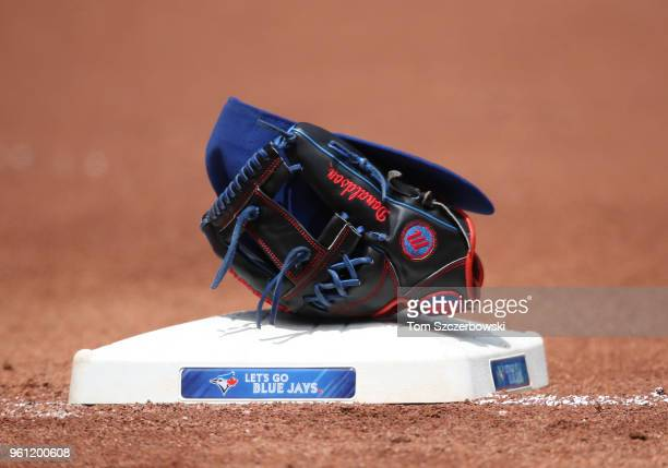 The glove and cap of Josh Donaldson of the Toronto Blue Jays rest on the third base bag during MLB game action against the Oakland Athletics at...