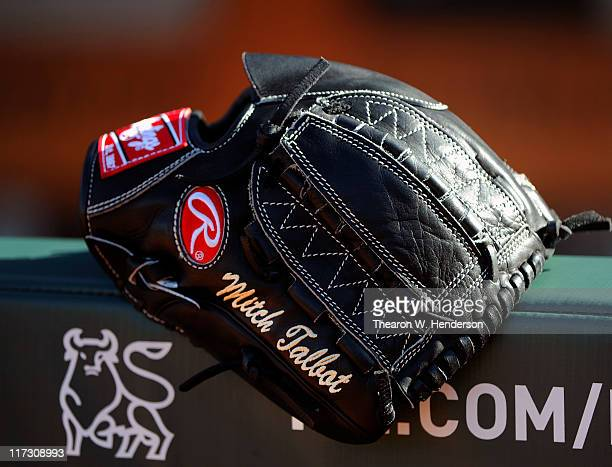 The glove of Mitch Talbot of the Cleveland Indians sits on the dugout rail during batting practice before a MLB baseball game against the San...