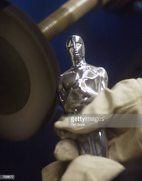 The gloved hands of Jose Irizarry buffs and polishes an Oscar statue made for the Academy Awards prior to its plating at the RS Owens manufacturing...