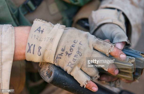 The gloves of Sergeant Kevin Boyd are seen as he gathers ammunition as US Marines of the 1st Light Armored Reconnaissance company as part of 1st...
