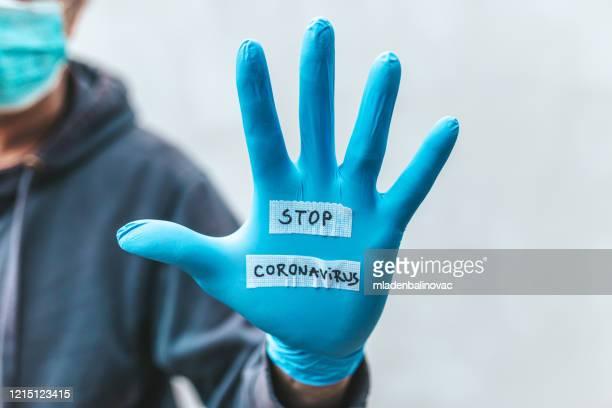 手袋着用者はコロナウイルスを停止するメッセージを持っています - ストップ ストックフォトと画像