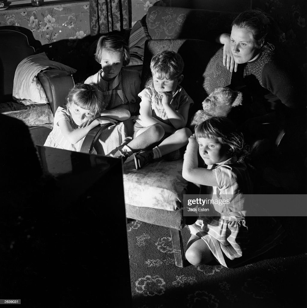 The glow of a television screen illuminates the faces of the group of children avidly watching it. Original Publication: Picture Post - 8974 - Blind Boy - unpub.