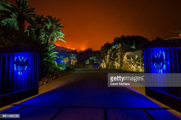 The glow of approaching flames is seen at the gates of an expensive home as the Thomas Fire continues to grow on December 12 2017 in Montecito...