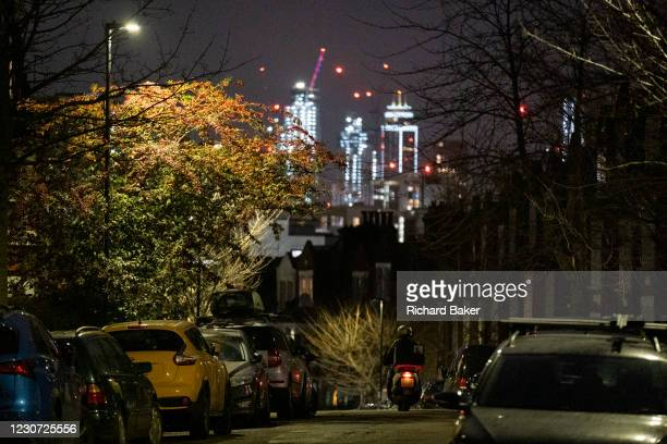 The glow of distant buildings overlooks a passing scooter rider and parked cars in a dark residential street in Herne Hill, south London on 21st...