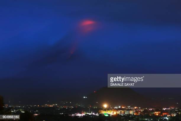 TOPSHOT The glow of lava from the cloudcovered Mayon volcano as it erupts is pictured from the Philippine city of Legazpi in Albay province early on...