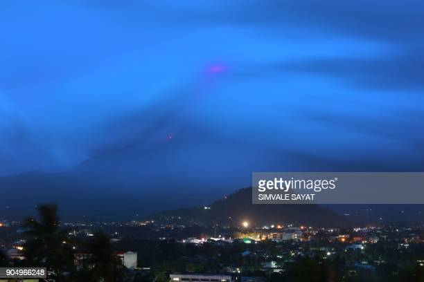 The glow of lava from the cloudcovered Mayon volcano as it erupts is pictured from the Philippine city of Legazpi in Albay province early on January...