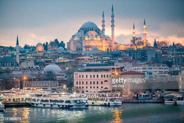 The glowing Suleymaniye Mosque sits on top of a hill overlooking the the city of Istanbul, Turkey as street lights begin to illuminate the twilight...