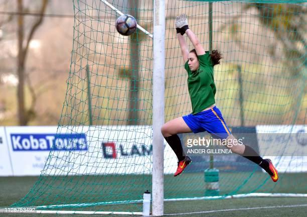 The goalkeeper of Anorga KKE football school's team jumps to clear the ball during a football match against Goierri Gorri team in the Spanish Basque...