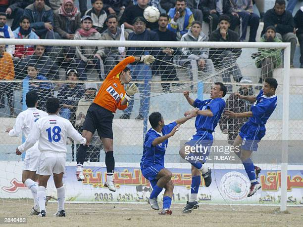 The goalkeeper of Baghdad's alZawra club Abbas Taleb deflects the ball in front of rival Baghdad team al Talaba's Saleh Sadir and two unidentified...