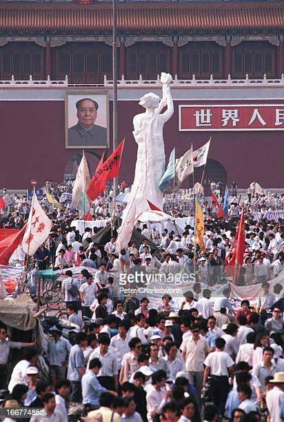 """The """"Goddess of Democracy"""" stands tall amid a huge crowd of flag waving pro-democracy demonstrators in front of the Mao Tse Tung portrait in..."""