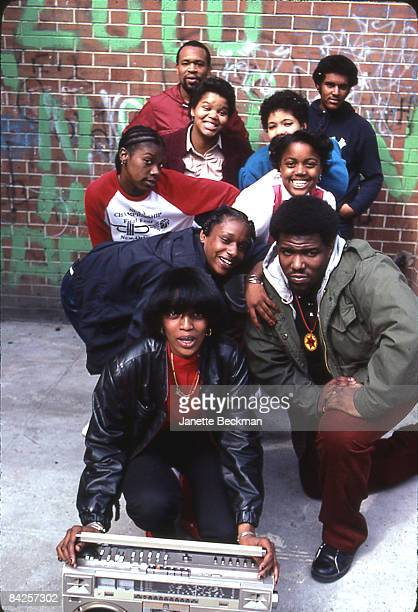 The 'Godfather of Hiphop' Afrika Bambaataa kneeling for a portrait with a group of friends in the Bronx 1983 A woman at the front of the group holds...