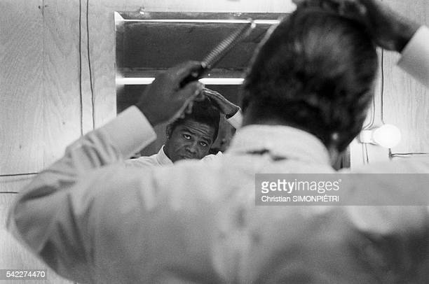 The 'Godfather of Soul,' James Brown combs his hair backstage before performing for American troops during the Vietnam War.