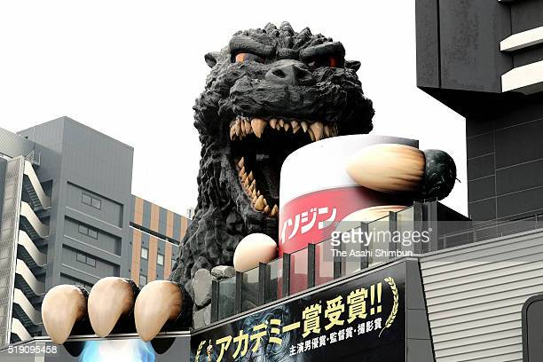 The Godzilla statue atop a roof of a shopping complex building holds a cup advertising gargling medicine on April 4 2016 in Tokyo Japan The Godzilla...