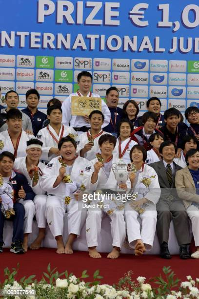 The gold medal winning Japanese team and reserves pose together after receiving their medals during the team event on day eight of the 2018 Judo...