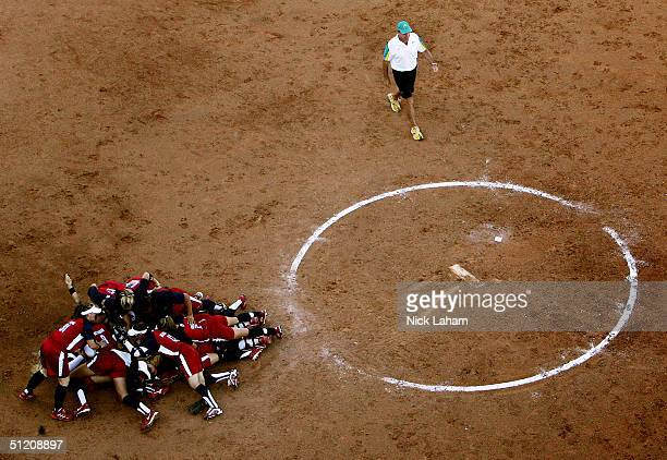 The gold medal winning team of the United States celebrates as head coach Simon Roskvist of Australia walks off the field in the softball gold medal...